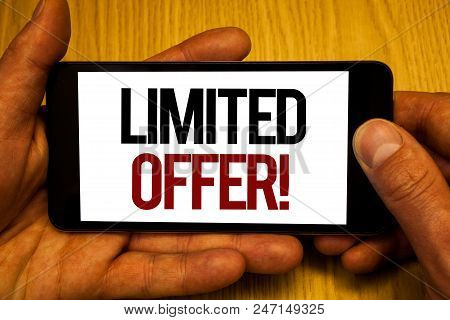 Text sign showing Limited Offer Motivational Call. Conceptual photo Short time special clearance Price Reduction Two hands holding black phone screen words written home button press stock photo