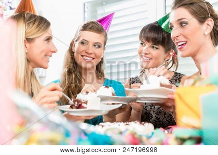 Beautiful female best friends with positive thinking and sense of humor sharing a birthday cake during a surprise celebration at home stock photo
