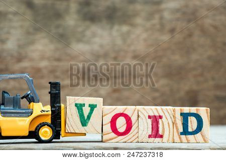 Yellow toy forklift hold letter block V to complete word void on wood background stock photo