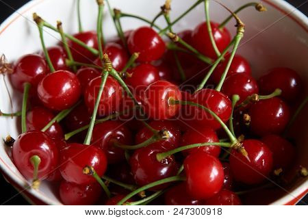 Bowl of fresh red cherries on dark background. Raw Red Organic Cherries food,  close-up, outdoors stock photo