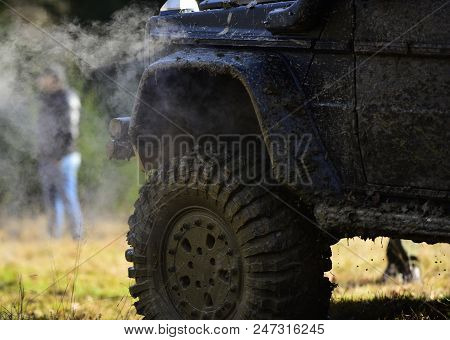 Part of vehicle covered with mud and man near it. SUV on nature background, close up. Side of car covered with dirt and cloud of smoke. Off road racing, force and extreme entertainment concept stock photo