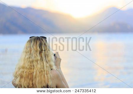 Blonde woman chechinig her smart phone during sunset stock photo
