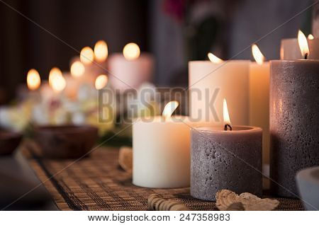 Closeup of burning candles spreading aroma on table in a spa room. Beautiful composition with grey a
