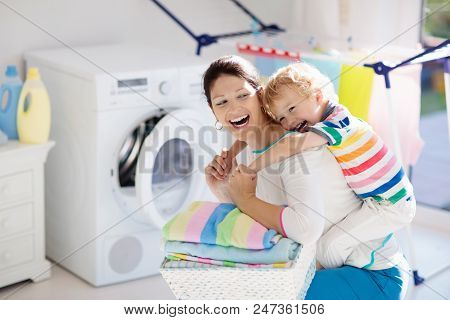 Mother and kids in laundry room with washing machine or tumble dryer. Family chores. Modern household devices and washing detergent in white sunny home. Clean washed clothes on drying rack. stock photo