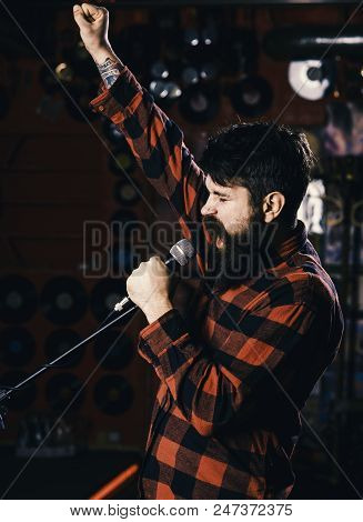 Musician with beard and mustache singing song in karaoke. Hipster likes to sing on stage. Man with enthusiastic face holds microphone, singing song, karaoke club background. Music and leisure concept. stock photo