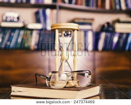 Scientists attributes concept. Hourglass counting time near old fashioned eyeglasses. Sand falling down inside of hourglass. Hourglass, old book and eyeglasses on wooden table, library on background. stock photo