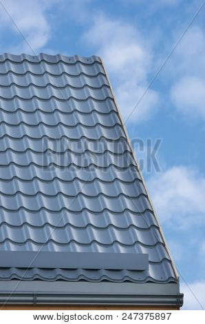 Grey Steel Tile Roof Texture Background, Gray Tiled Roofing, Large Detailed Vertical Closeup, Modern Residential House Rooftop Tiles Detail Textured Pattern, Bright Sunny Sky Summer Cloudscape Clouds Copy Space, Property Concept Real Estate Metaphor stock photo
