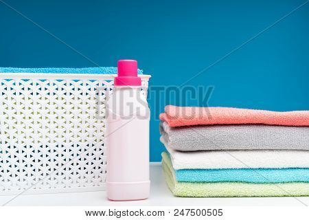 Close up of white board with softened colorful bath linens folded in pile. Plastic clothesbasket and bottle of pink softener are lying aside stock photo