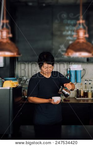 Asian woman 40s white skin work as a barista pouring latte froth to make a coffee latte art into the white coffee cup for serve to customers in the coffee shop cafe stock photo