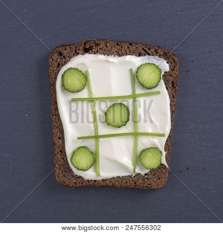 Vegetarian sandwiches with cream cheese, cucumbers and parsley, healthy snack on black slate background, close up, top view. Tic Tac Toe game with food stock photo