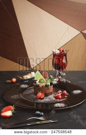 Exquisite restaurant mousse dessert. Chocolate and vanilla souffle on walnut biscuit served on glass plate finely decorated with fresh berries and mint. Exclusive meals and haute cuisine concept stock photo