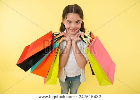 Fashion expert. Child cute shopping expert helps carry packages during shopping. Little shop expert. Girl shopaholic likes shopping. Kid girl happy face carries bunch packages yellow background. stock photo