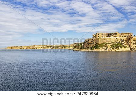 Scenic Mediterranean view of part of Bighi Hospital and Fort Ricasoli and St. Elmo breakwater lighthouse in the distance, at Grand Harbor, Malta stock photo