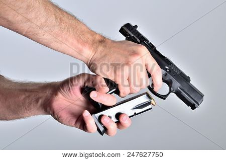 Detail of man's hand reloading pistol after shooting stock photo