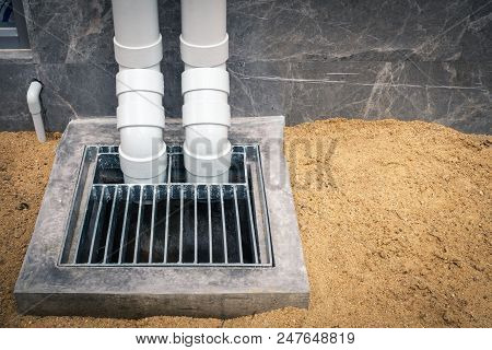 PVC pipeline roofing drainage downspout and concrete manhole at construction site. stock photo