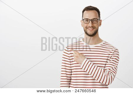 Portrait of satisfied happy aduly man with bristle in trendy glasses and striped pullover, pointing at upper left corner while smiling broadly, showing positive opinion and directing at great place. stock photo
