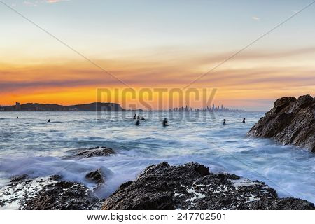 Ocean tide washing over the rocks at Currumbin Rock with a colourful sunset in the skies and surfers in the ocean. stock photo