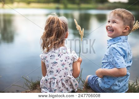 Your Happy Couple Of Kids, Boy Gives Wheat Spikelets Girl. Children Are Sitting Near Lake, Outdoor At Park. Autumn And Summer Season. Happy Family Values. Children's Health Care stock photo
