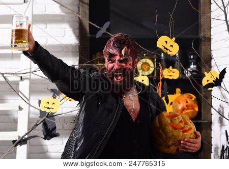 Devil or monster partying. Halloween party concept. Man wearing scary makeup holds mug of beer with Halloween decor on background. Demon with horns and smiling evil face holds jack o lantern stock photo