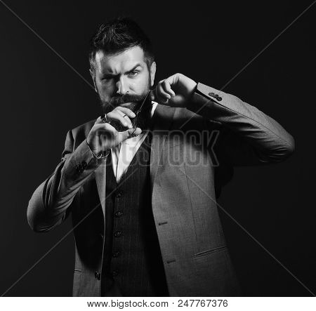 Business reduction concept. Businessman with confused face on dark red background. Man with long beard holds steel scissors. Macho in formal suit holds and cuts beard and moustache. stock photo