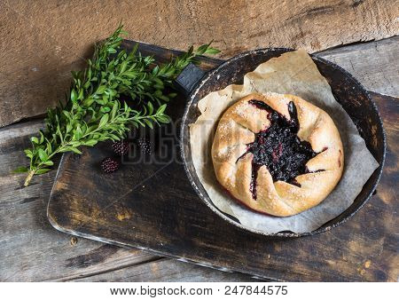 Summer galette with berries, raspberry, blueberry, blackberry, apple and crusty sugar vegetarian dough on blue background. Summer food, summer pie on parchment paper. Open pie. Vegan food. stock photo