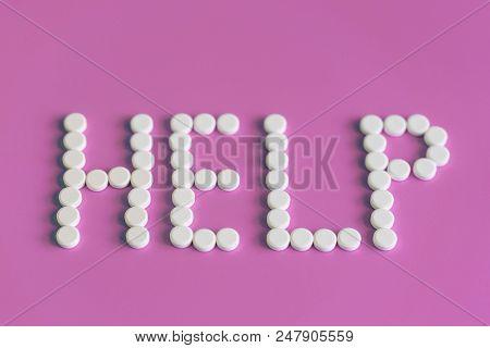 White pills on blue background word help. White medical pills on a pink background. Help word concept. stock photo