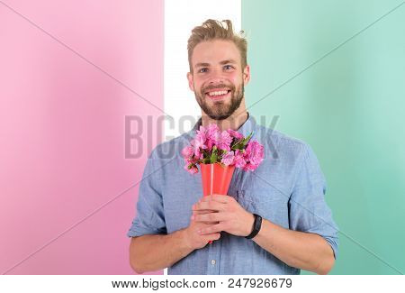 Best flowers for her. Macho holds bouquet as romantic gift. Guy bring romantic pleasant gift waiting for her. Man ready for date bring pink flowers. Boyfriend happy holds bouquet waiting for date. stock photo