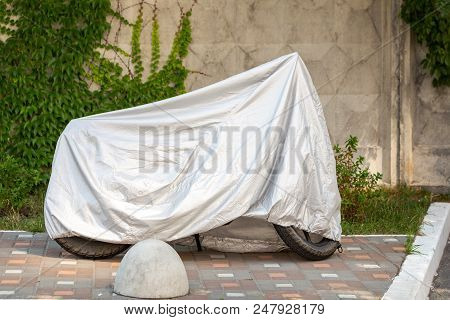 Motorcycle covered with grey protective jacket . Scooter with fabric shield parked at pavement near concrete wall. Waterproof parking outdoors during travel. stock photo
