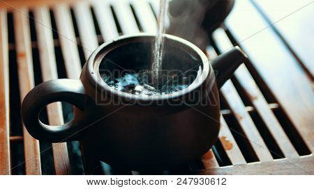 Chinese tea ceremony with puerh tea, Brewing black Shu Puer in pot from Ixin clay, boiling water pours into kettle, close up with selective focus stock photo