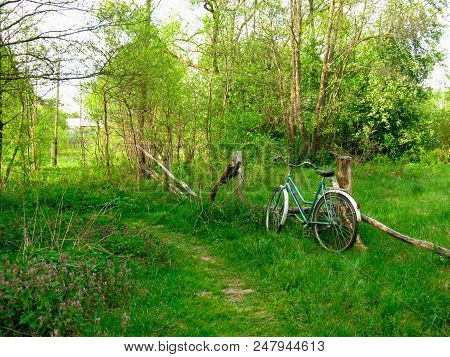 An old vintage bicycle stands leaning against a broken fence. The cyclist made a rest on the way. stock photo