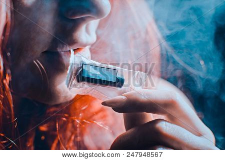 Red-haired sexy girl in a cafe dressed in red dress smoking a hookah. Toned image. Concept of pleasant spending time and female beauty. girl prints the mouthpiece packing with teeth close up stock photo