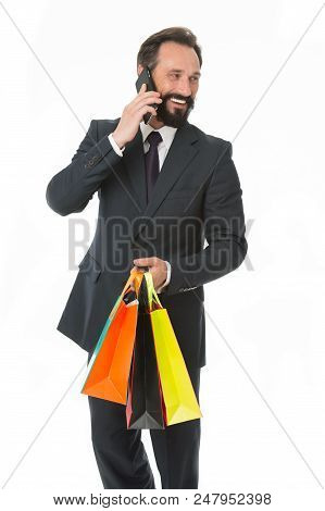 Family always on his mind. Busy businessman talk phone buy gifts for his family. Man calling family while shopping isolated white background. Man classic suit happy carries shopping bags. Bought gift. stock photo