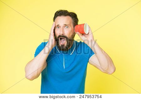 Shocking rumors. Man bearded mature guy eavesdrops with cup yellow background. Find out new scandalous rumors first. Guy shocked eavesdrops scandalous rumors. Curiosity and impoliteness. stock photo
