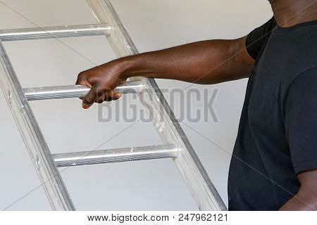 An electrician holds an aluminum ladder. The builder carries an aluminum stepladder on gray background. Worker of the plant with aluminum rung ladder stock photo