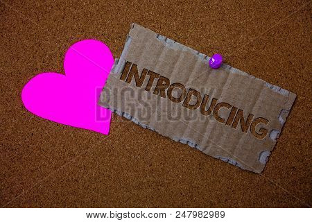 Conceptual hand writing showing Introducing. Business photo text Presenting a topic or someone Initial approach First meeting Brown old damaged paperboard ideas pink heart cork background stock photo