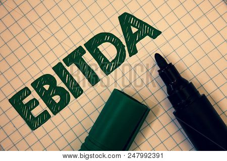 Text sign showing Ebitda. Conceptual photo Earnings Before Interest Taxes Depreciation Amortization Abbreviation Squared paper open marker ideas messages inspirational thoughts feelings stock photo