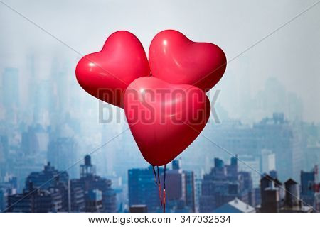 Valentines day in the New York city. Three red balloons in form of heart flying over Manhattan and skyscrapers. Сoncept. America. USA. Aerial view. stock photo