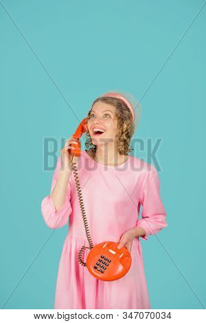 Happy woman talking at retro handset. Woman talking on retro phone. Girl talking on landline phone. Smiling woman in pink dress with telephone handset. Happy woman holds handset. Communication. stock photo