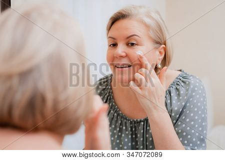Happy healthy Mature woman at mirror apply anti aging moisturizing cosmetic cream on face, smiling middle-aged lady soft clean skin care and beauty at home. stock photo