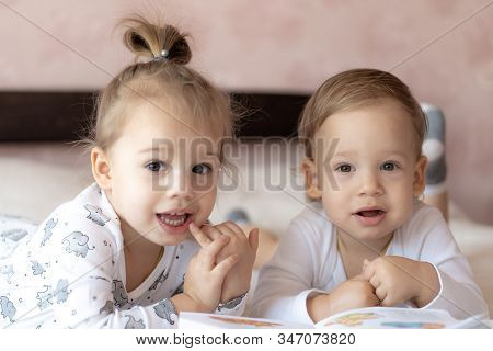 Lovely children - brother and sister, reading a book, on the bed. Close up of children in bed reading a book. A boy and a girl in white are playing on the bed. Babies in white on the bed. Cute kids. stock photo