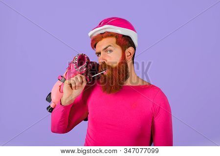 Bearded man with roller-skates. Man with roller skates and helmet. Active sport. Roller skating ride. Healthy lifestyle. Holidays. Vacation. Protective sport helmet. Protective sport equipment stock photo