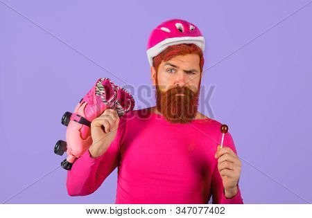 Serious man with roller skates and helmet. Active sport. Roller skating ride. Healthy lifestyle. Bearded man with roller-skates. Holidays. Vacation. Protective sport helmet. Protective sport equipment stock photo