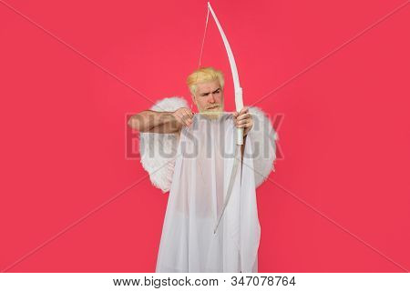 God of love. Cupid. Amour. Cupid with bow. February 14. Cupid angel with bow and arrows. Symbol of love. Happy Valentines Day. Serious man in angel costume. Valentines day angel. Cupid shoot with bow stock photo