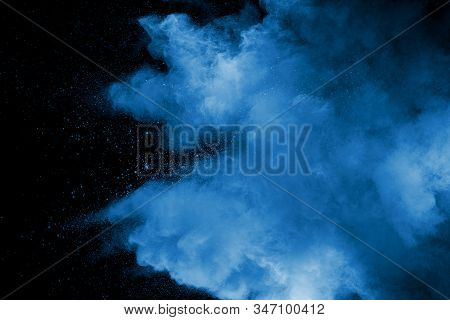 Abstract art blue powder on black background. stock photo