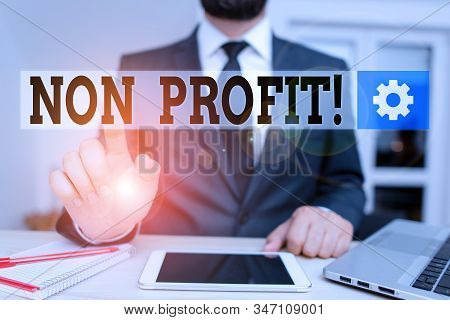 Word writing text Non Profit. Business concept for not making or conducted primarily to make profit organization Male human wear formal clothes present presentation use hi tech smartphone. stock photo