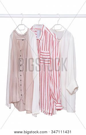 Hanging blouses isolated. Closeup of collection of three female various colorful blouses on a clothes rail isolated on a white background. Womens summer fashion. stock photo