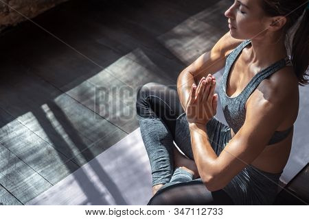 Calm fit sporty healthy mindful woman sit in lotus pose doing yoga exercise breathing fresh air meditating in studio lit with sunlight, stress free peace of mind concept, copy space, close up view stock photo