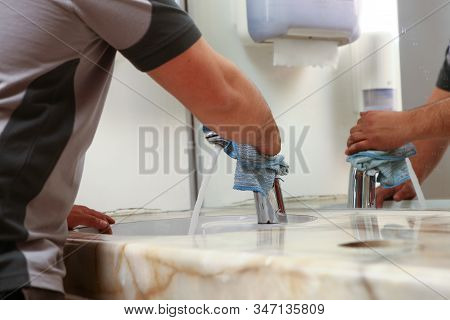 cleaner with rags cleaning a bath room sink, hands and cleaning rag stock photo