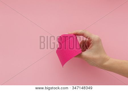 Tired hand with violet kinesiology tape isolated on pink background. Physiotherapy tape for wrist pain, aches and tension. elastic therapeutic tape. adhesive tape and alternative medicine. stock photo