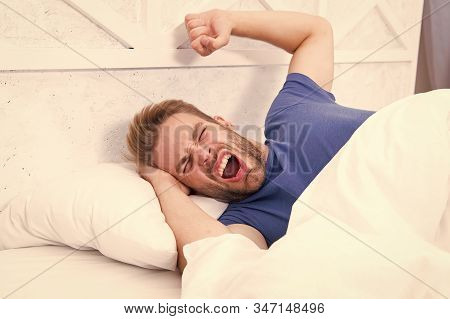 Comfortable place to pass out. Sexy man lying in comfortable bed. Handsome guy yawning and feeling comfortable after waking up in morning. Making more comfortable by lying. stock photo